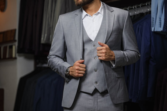 Modern young handsome businessman looking and choosing classical suit in the suit shop