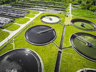 Sewage farm. Static aerial photo looking down onto the clarifying tanks and green grass. Geometric background texture.