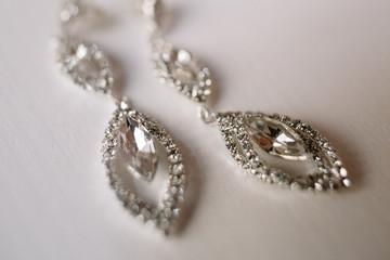 Crystal earrings lie on white table