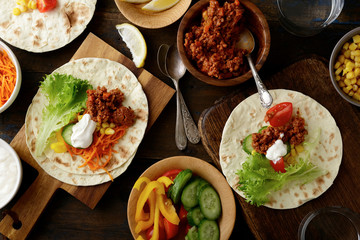 Different mexican Tacos with ground meat, carrots, cucumber, corn, pepper, tomato and lettuce