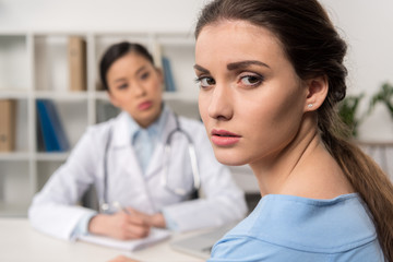 portrait of upset patient looking at camera with doctor sitting at workplace behind