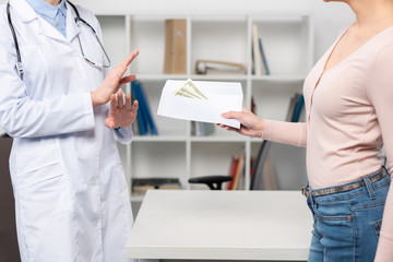 Cropped shot of patient giving envelope with dollar banknotes to doctor in white coat
