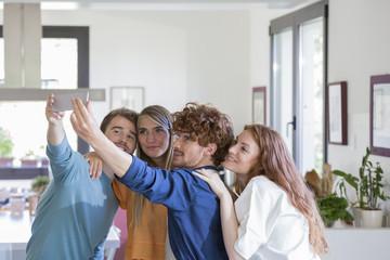 Friends taking selfies in kitchen