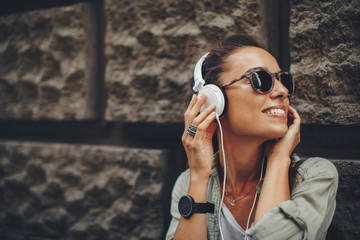 Happy young woman listening to music via headphones on the street on a sunny day