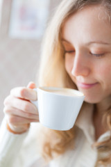 Coffee. Beautiful smiling girl holding in hand a cup of coffee