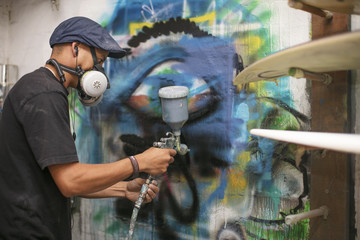 Surfboard shaper workshop, surfshop employee spray painting wall design