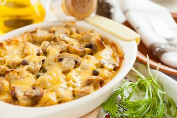 Baked mushrooms, potatoes and cheese on a pan closeup