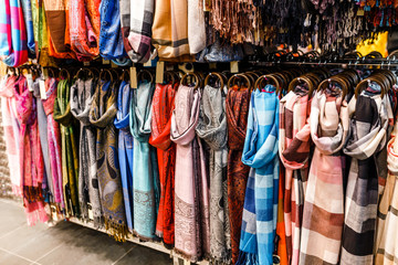 Many bright female scarfs and shawl close-up at shop