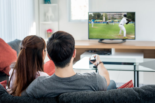 Young Asian couple waching baseball sport on tv at home