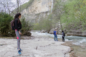Young travelers standing together by the creek and looking away at a view. Travel adventure and hiking activity, healthy lifestyle on summer vacation and weekend tour