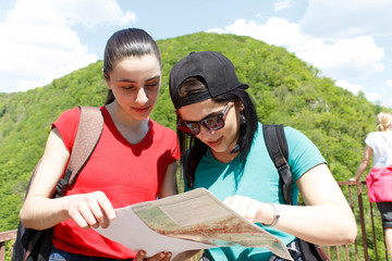 Two young Tourists With Backpacks travel, looking a paper map