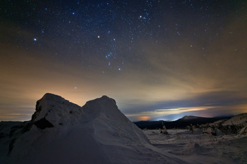 The constellation of Orion over the mountains on a winter night.