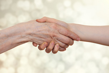 Handshake between an old person with a wrinkled hand and a kid, isolated on white background