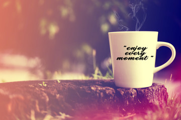 "White cup on wooden background. Written ""Enjoy Every Moment""."