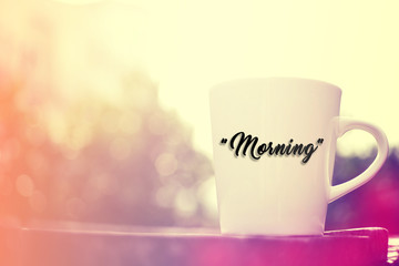 "White cup on wooden background. Written ""Morning""."