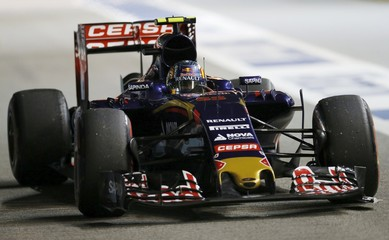 Toro Rosso Formula One driver Carlos Sainz of Spain returns to the pit lane with a damaged car during the qualifying session of the Singapore F1 Grand Prix night race in Singapore