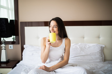 Beautiful woman drinking a coffee sitting on her bed at home in the morning