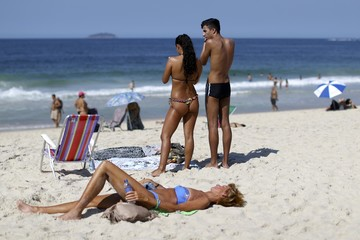 Sunbathers enjoy the sunny weather on Copacabana beach in Rio de Janeiro