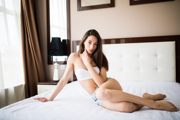 portrait of young beautiful woman on bed at home