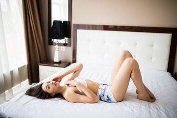 happy girl lies on a bed. Happy young woman lying on the bed with legs