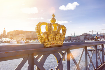 Skeppsholmsbron (Skeppsholm Bridge) with famous golden crown with royal palace in the background in Stockholm, Sweden