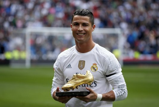 Real Madrid's striker Cristiano Ronaldo poses with his fourth Golden Boot trophy before their Spanish First Division soccer match against Levante at Santiago Bernabeu stadium in Madrid,
