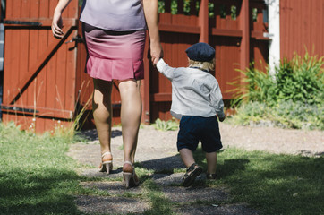 Rear view of mother walking with son