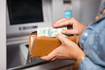 Close-up of a woman keeping money in her purse