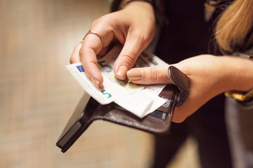 Close-up of a woman's hand holding wallet with banknotes and receipts