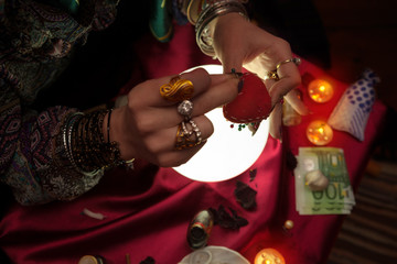 Woman fortune teller point a needle pin to handmade heart