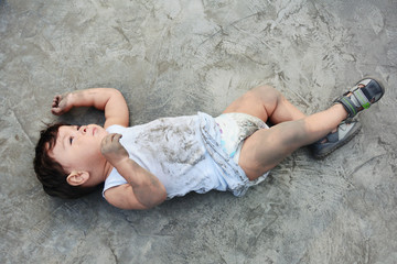 Little dirty baby boy lying on the muddy floor