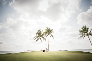 Two friends play golf at a beach resort