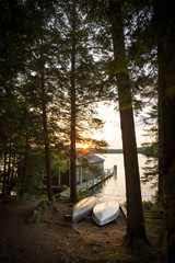 Boat house with canoes and a dock on the lake at sunrise. New Hampshire