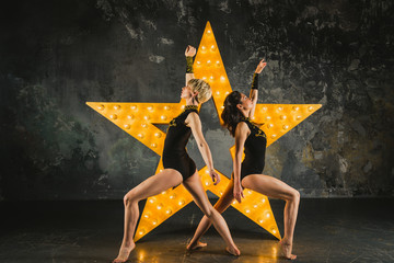 Girls dance against the backdrop of a glowing star