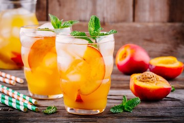 Summer cold drinks: homemade peach lemonade with ice cubes, and mint in glasses