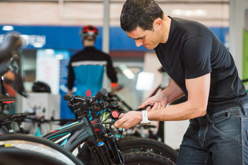 Male master is fixing the bicycle in a special workshop