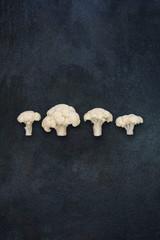 Four small cauliflowers isolated on dark gray slate stone background