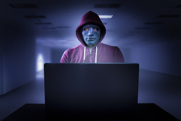 Hacker with mask in front of a laptop