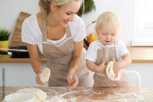 Mother and her little daughter cooking holiday pie or cookies for Mother's day. Concept of happy family in the kitchen