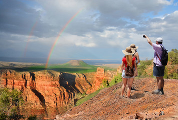 Family  hiking on vacation, taking pictures with phone and  relaxing on top of the mountain, looking at beautiful rainbow at sunset , mountains landscape. Grand Canyon National Park, Arizona, USA.
