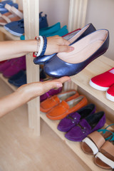 Rows of colorful women's shoes (ballet shoes) in the wardrobe. Selective focus