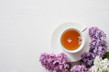 Cup of tea and flowers of a lilac on a white wooden surface, top view