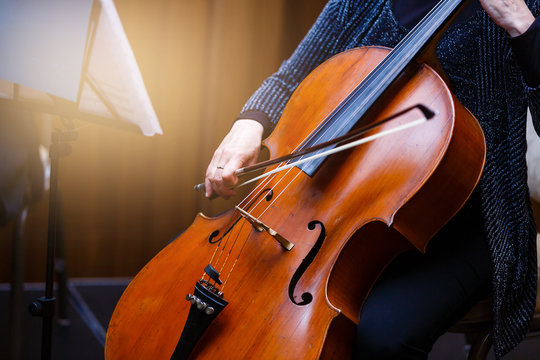 A young girl plays the cello in the dark. Hands on cello