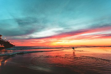 Surfer running on the beach during sunset