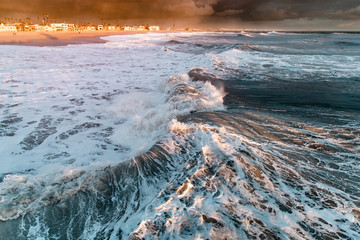 View of big waves in sea at sunset