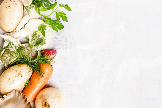 Raw potatoes, oyster mushrooms, carrots, onions, parsley, garlic and dill, food background, top view