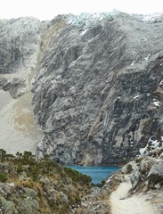 Thin hiking trail leading to the beautiful turquoise waters of laguna 69 surrounded by the steep cliffs and mountains.