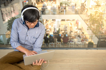 Young Asian man dressed in casual style using laptop computer while listening to music. Digital nomad working in co working space, modern IT lifestyle with work life balance concept.