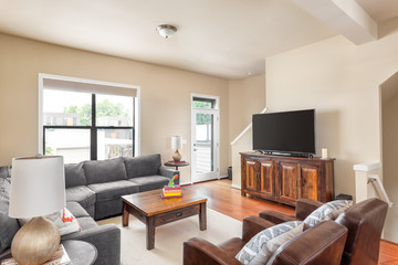 Beautiful living room in new condominium with television, couches, chairs, and coffee table