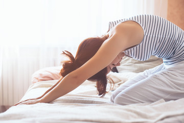 Woman doing yoga in the bed